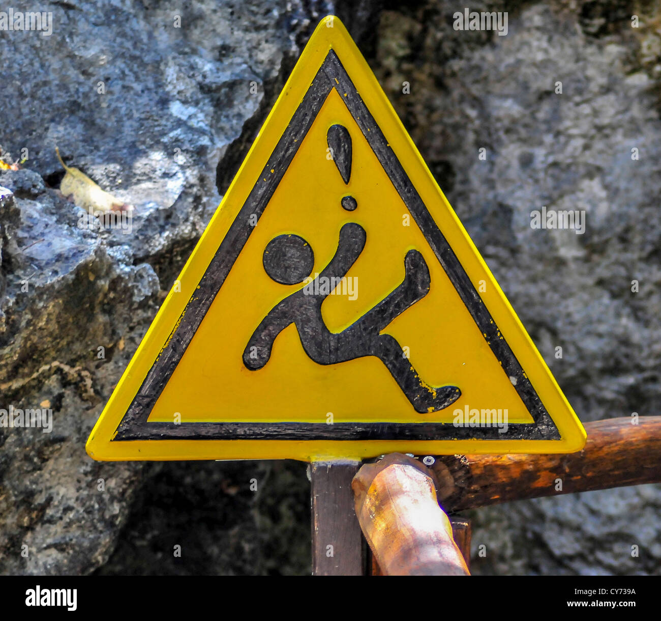 A yellow triangular slippery when wet warning sign in México Mexican with an ideogram of a falling figure triangle - Stock Image