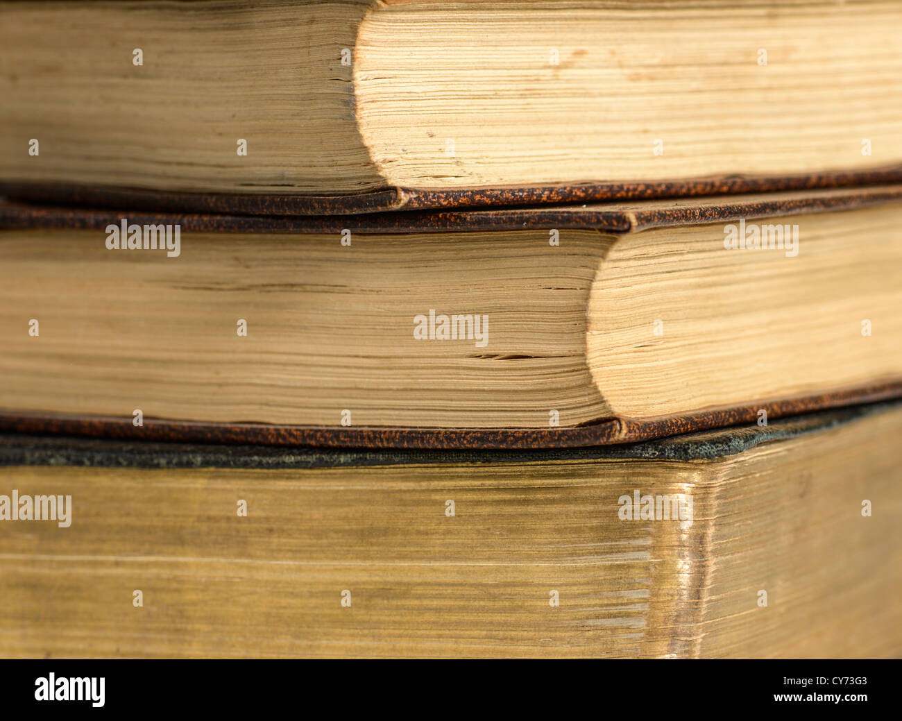 A stack pile of three antique vintage old books showing signs of wear and tear anonymous anontmised anonymized Stock Photo