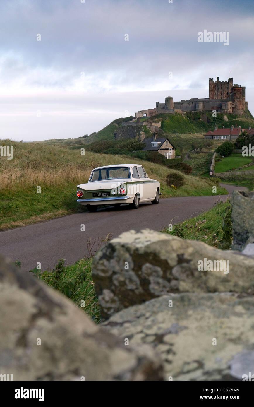 1965 Ford Lotus Cortina at Bamburgh castle Nothumberland UK Stock Photo