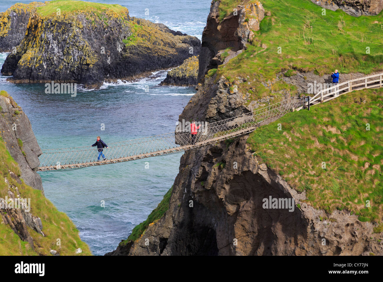People walking on Carrick-a-Rede Rope Bridge from Carrick Island to the mainland in County Antrim, Northern Ireland, - Stock Image