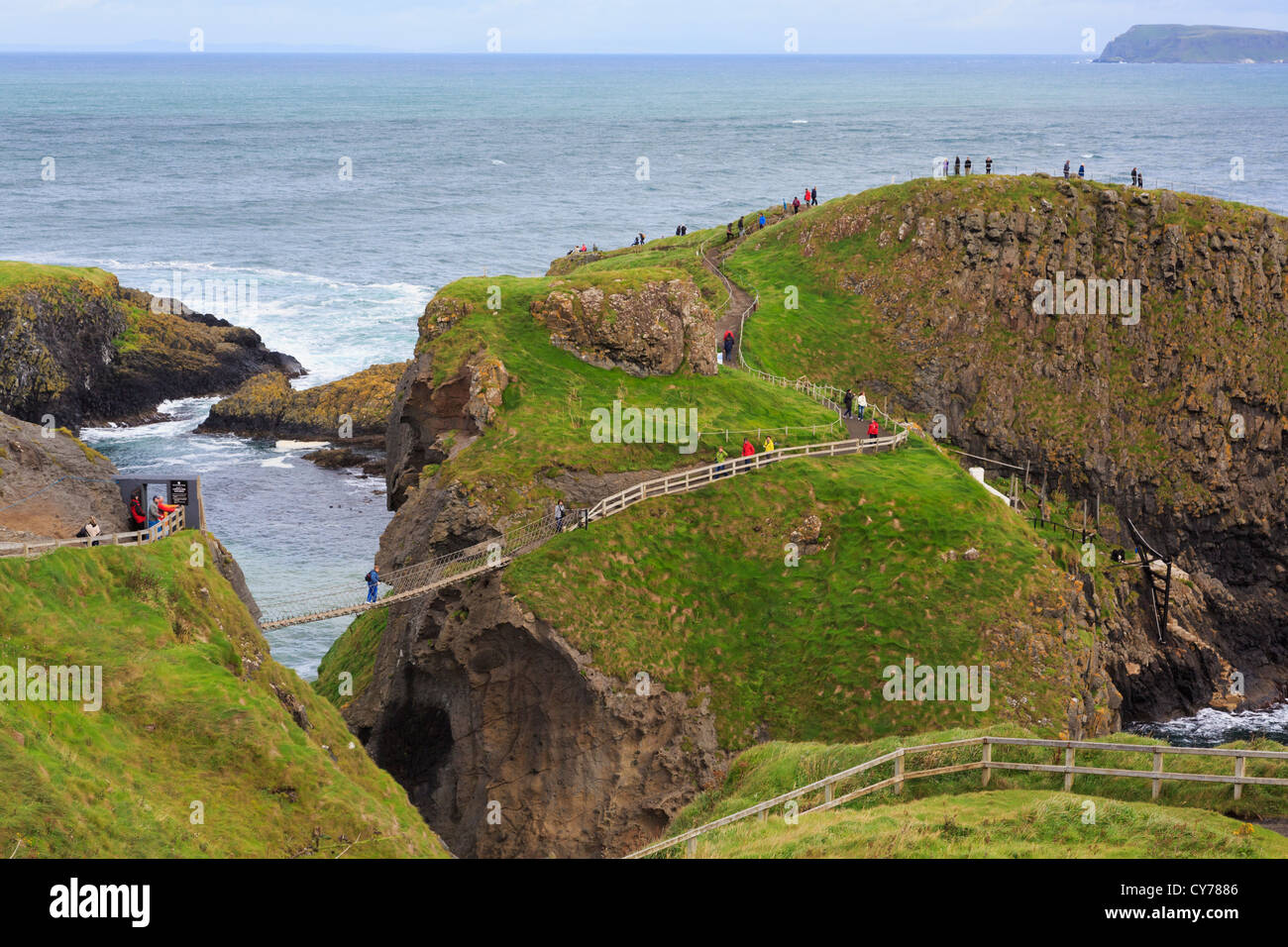 Tourists on Carrick Island with Carrick-a-Rede Rope Bridge on the north Causeway Coast in County Antrim, Northern - Stock Image