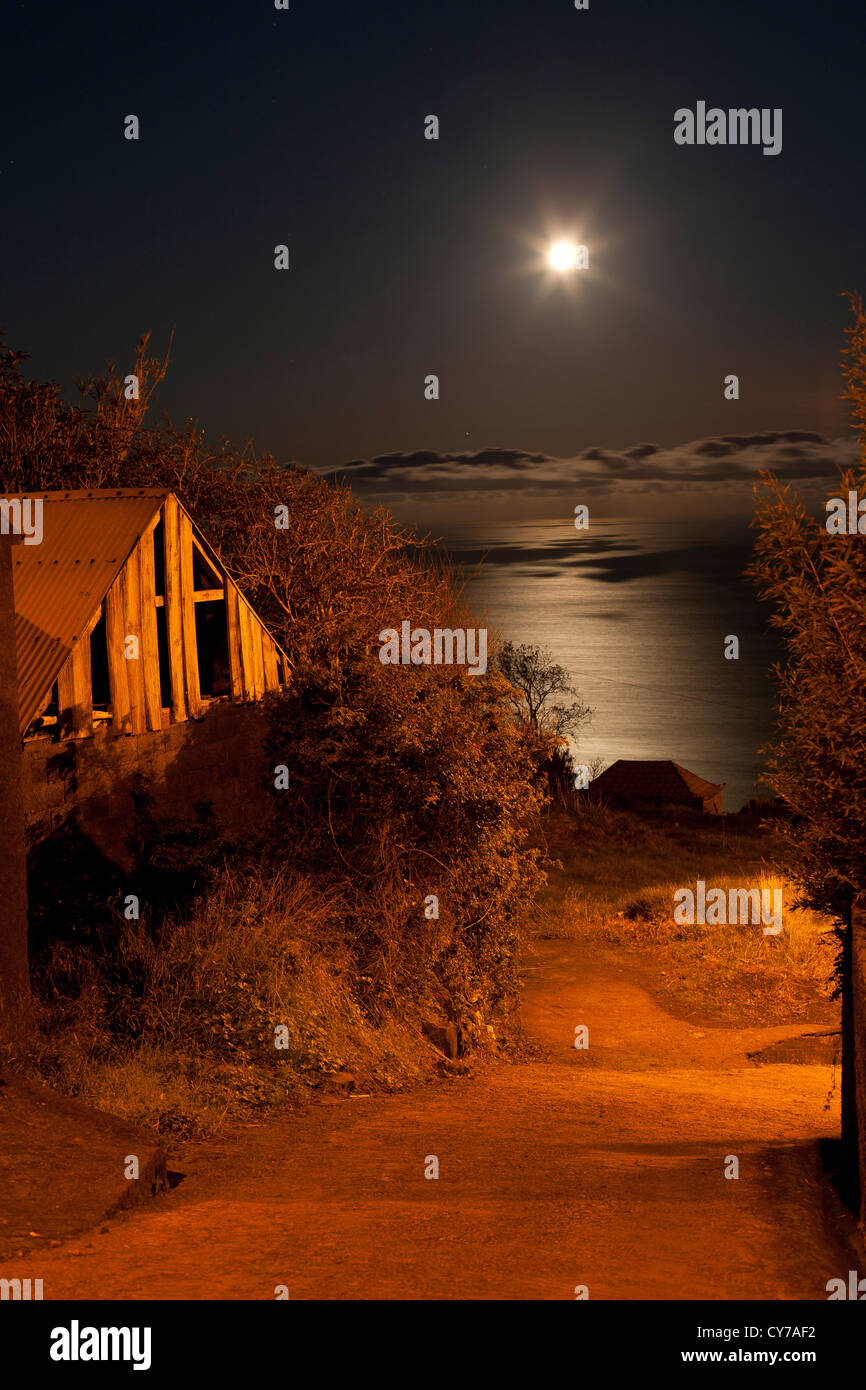 Night in a rural location on the Western side of Madeira island with the moon in the sky over the Atlantic Ocean. - Stock Image