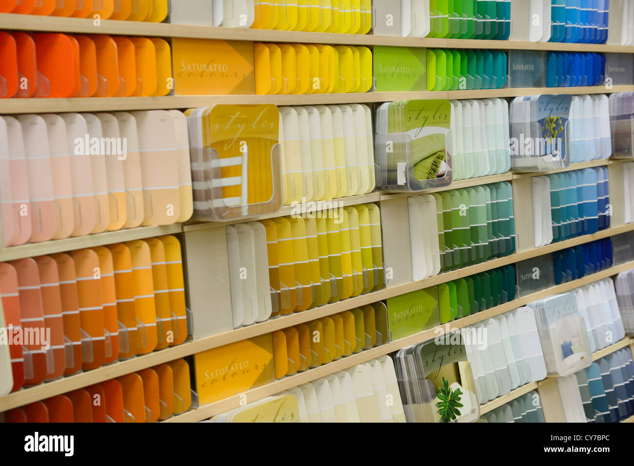 Spectrum of color coded paint chip samples on a display shelf in a hardware store - Stock Image