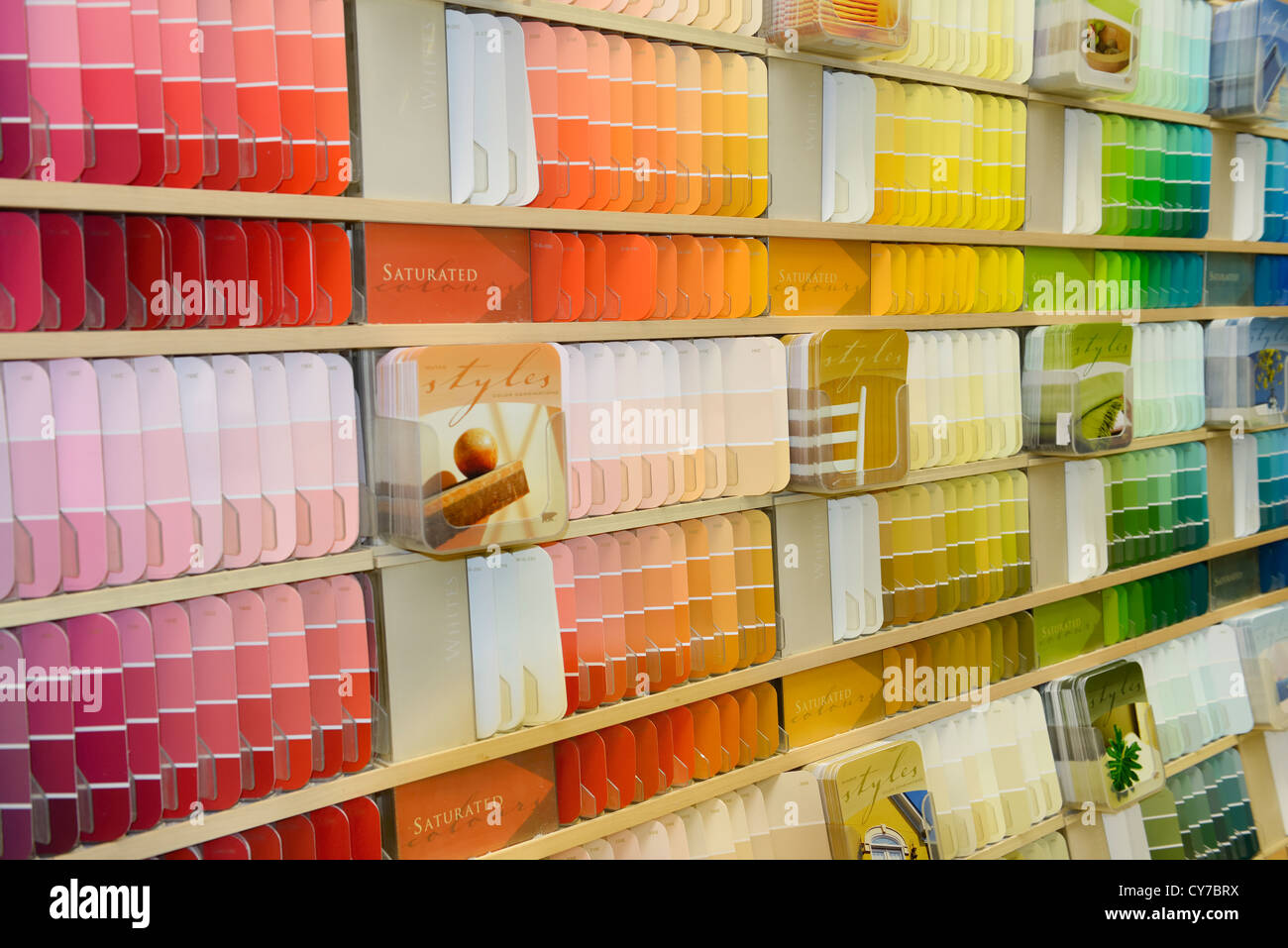 Selection of color coded paint chip samples on a display shelf in a hardware store - Stock Image