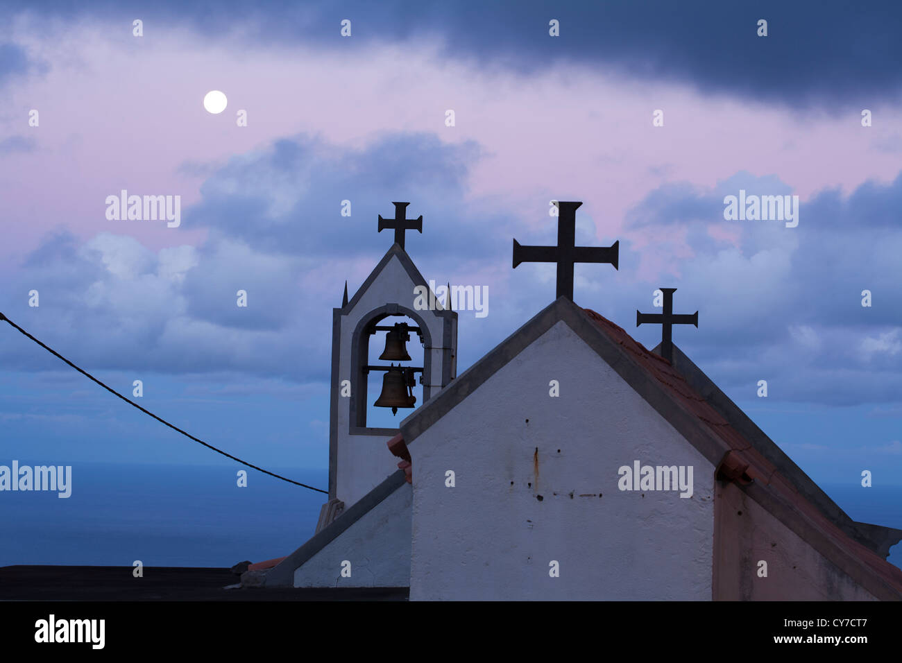 The roof and bells of the chapel at Cabo, Ponta do Pargo, Madeira, with the moon in in the background. - Stock Image