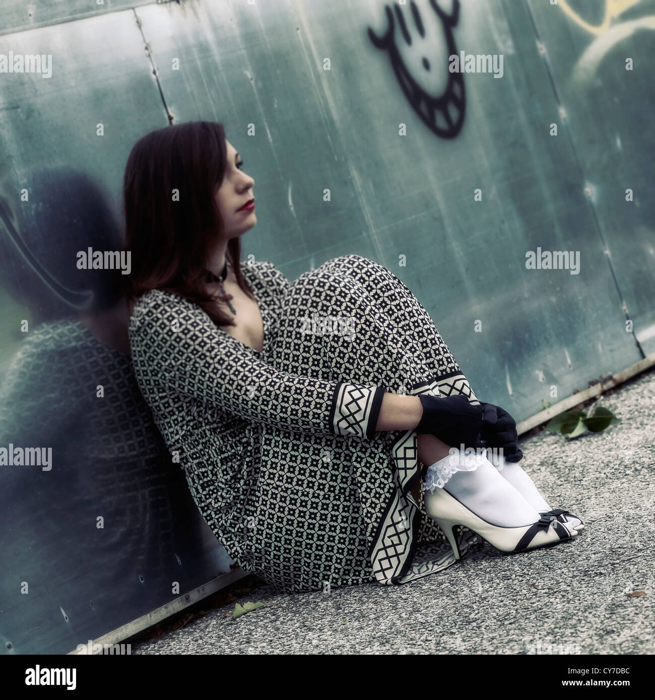 a woman is sitting on a street, leaning against a graffiti wall - Stock Image