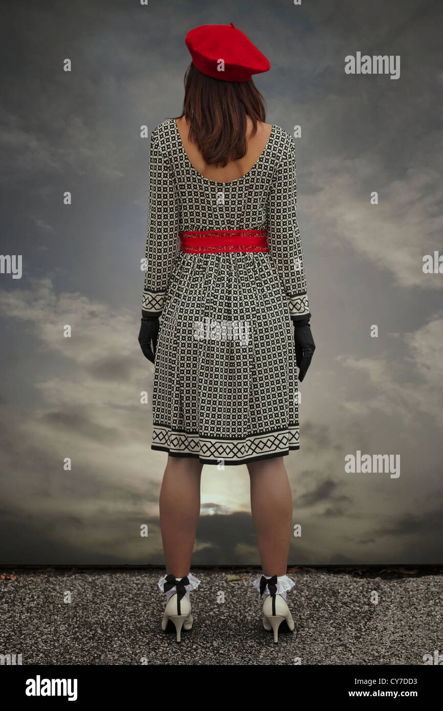 a woman in a black and white dress with a red cap is standing at the edge of a roof - Stock Image