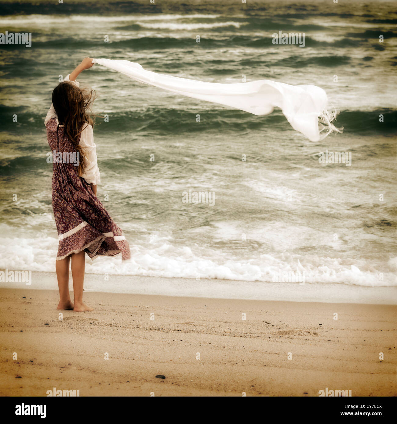 a girl standing on the beach and lets fly a scarf - Stock Image