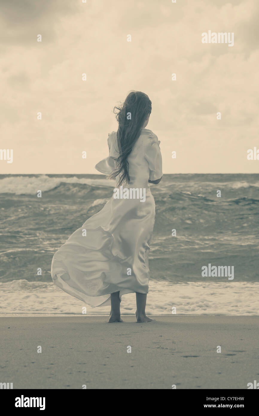 a girl in a white dress is standing alone at the wild, rough sea - Stock Image