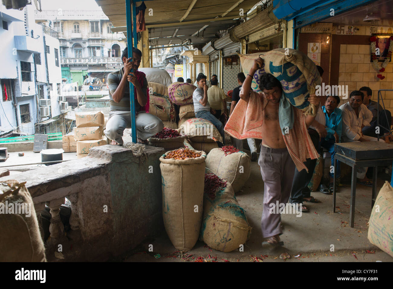 Porter carrying a large burlap sack on a verandah above an alley off Khari Baoli Road (Spice Market Bazaar off Chandni - Stock Image