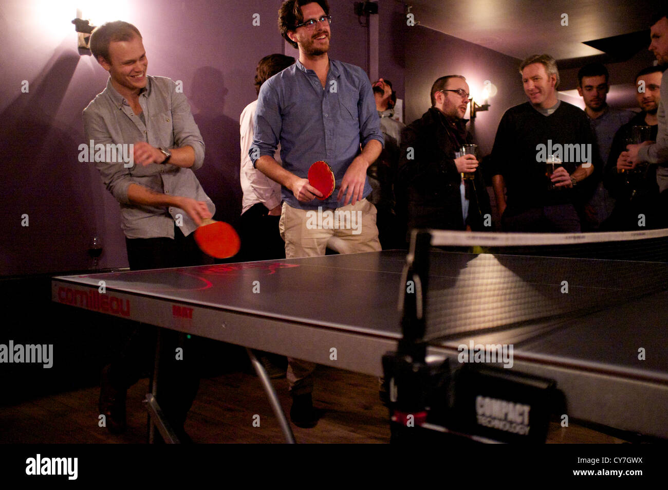 Bearded man playing table tennis in a pub in the trendy Clerkenwell area of London. - Stock Image