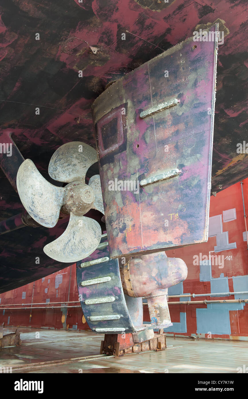 ship propeller and rudder in dry dock - Stock Image