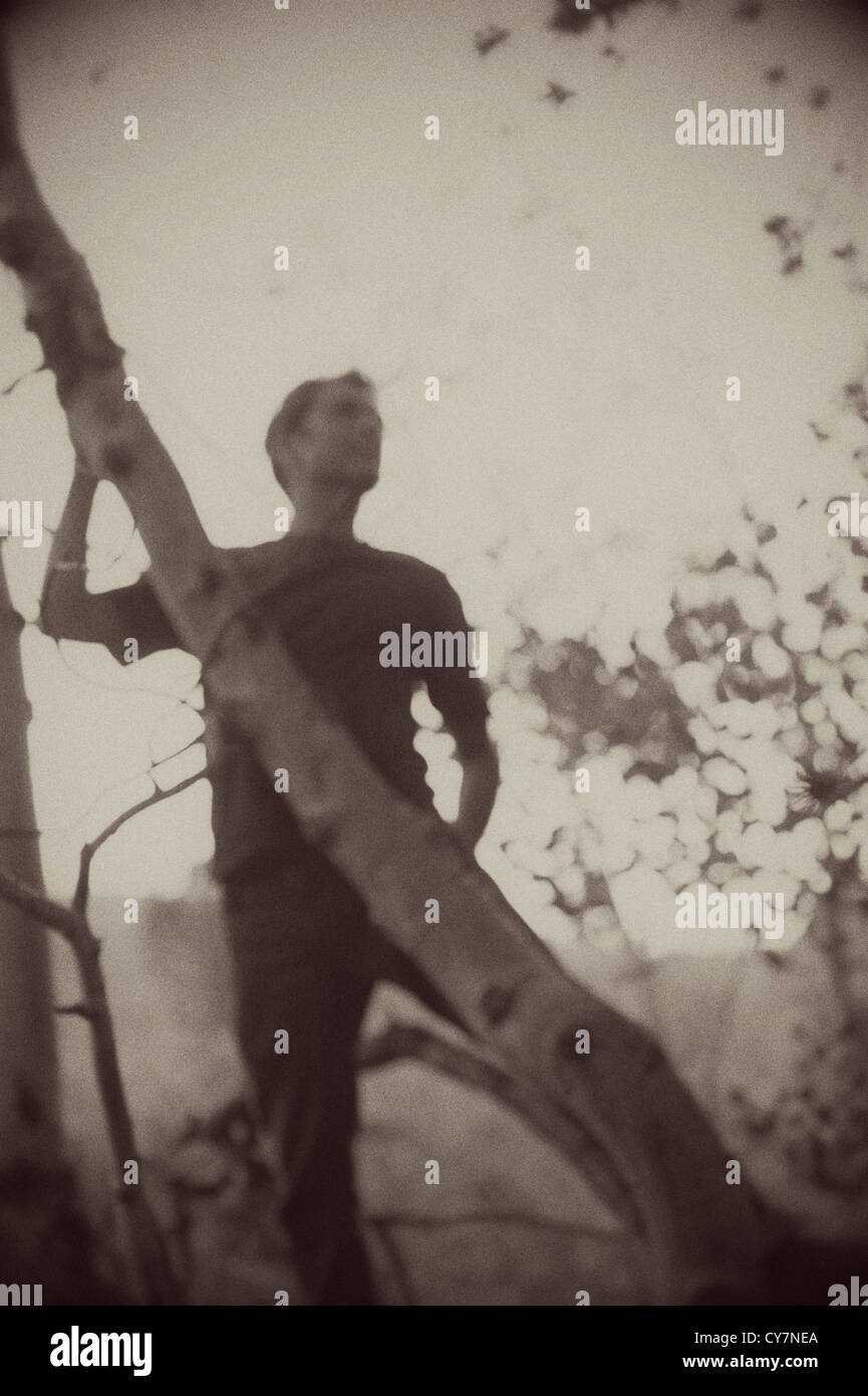 Blurred sepia toned silhouette of a man in the forest. - Stock Image