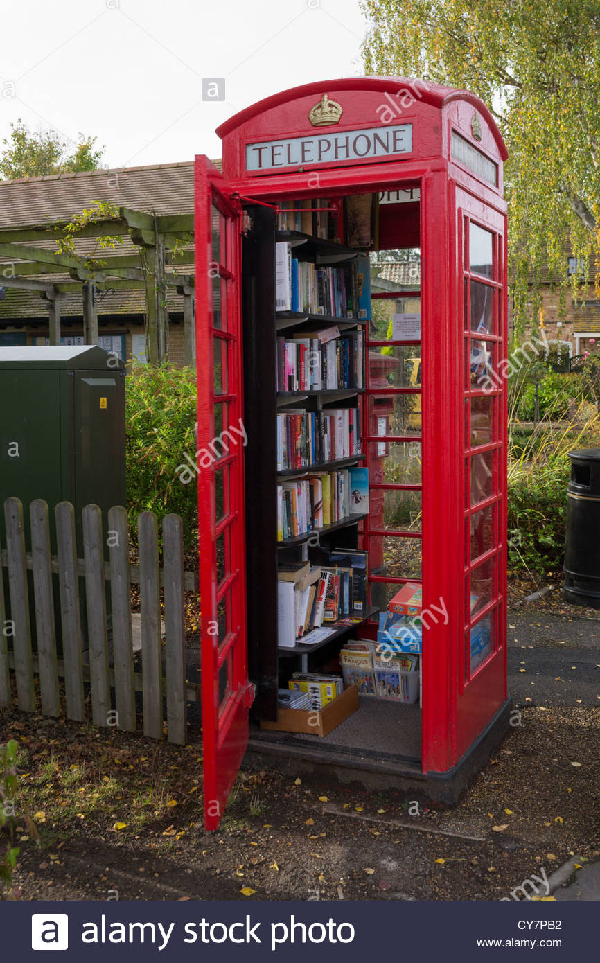 A community library in an old red telephone box in Hemingford Abbotts, Cambridgeshire - Stock Image