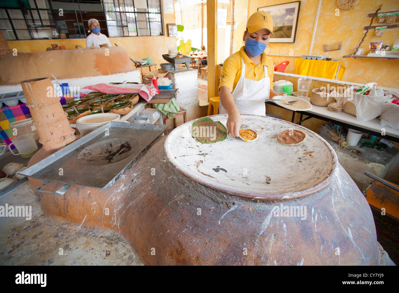 Cooks at the Itanoní eatery in Oaxaca, Mexico prepare various corn-based dishes on a clay oven. - Stock Image