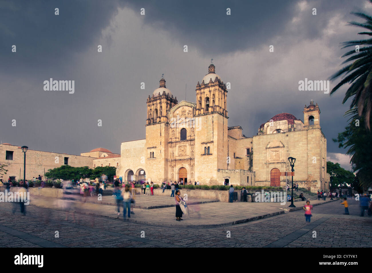 People mull around the Santo Domingo church as a thunderstorm approaches in Oaxaca, Mexico. - Stock Image