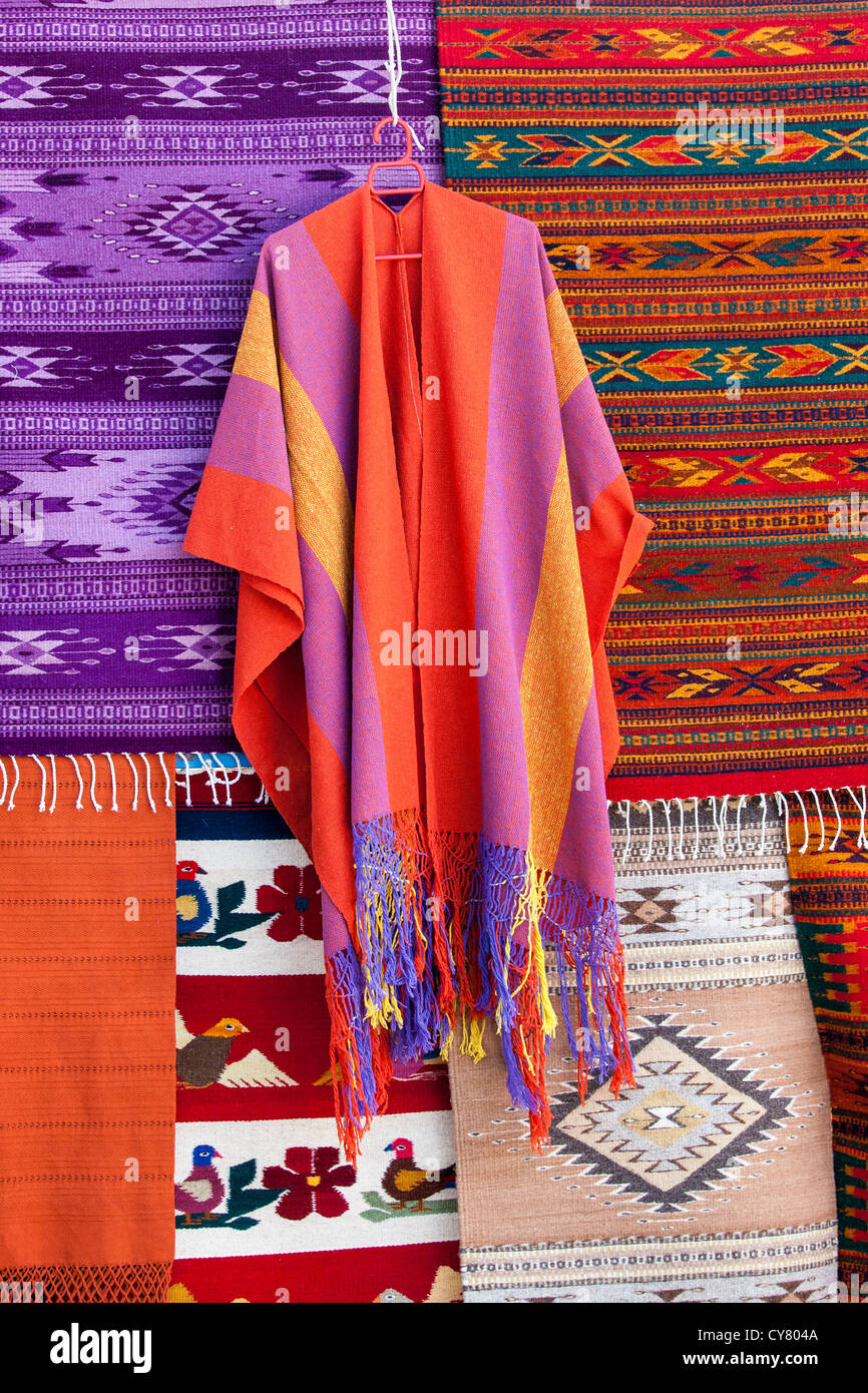 A poncho and rugs for sale in Teotitlan del Valle, Oaxaca, Mexico. - Stock Image