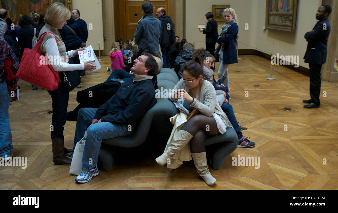 © PAUL TREACY (.COM) 2012. Tourists and Parisians take a break in the halls of the Louvre Museum in Paris, France. Stock Photo