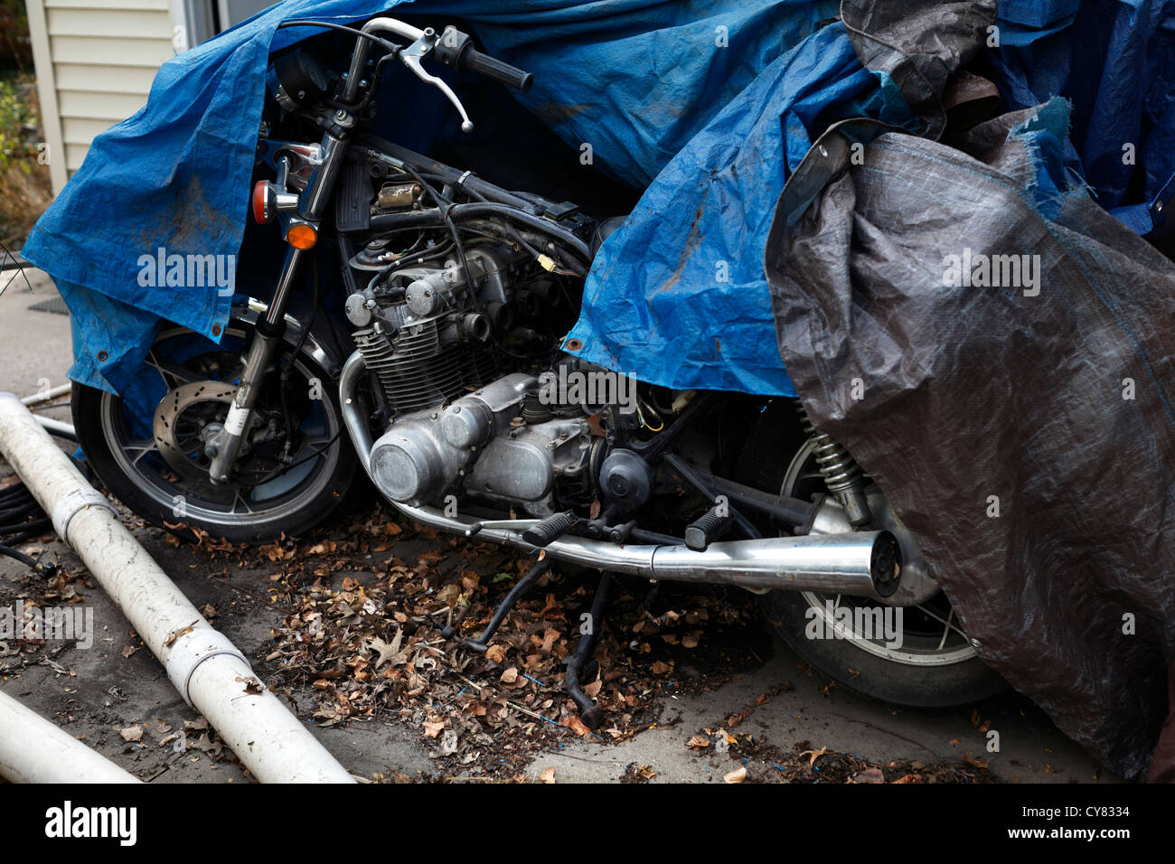 Incomplete motorcycle under blue tarp. - Stock Image