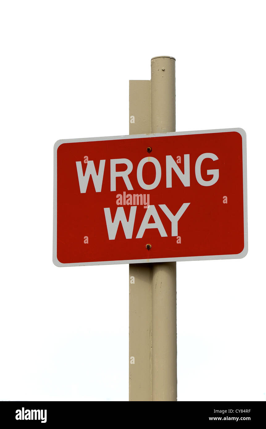 Red Wrong Way sign on a post against a white background - Stock Image