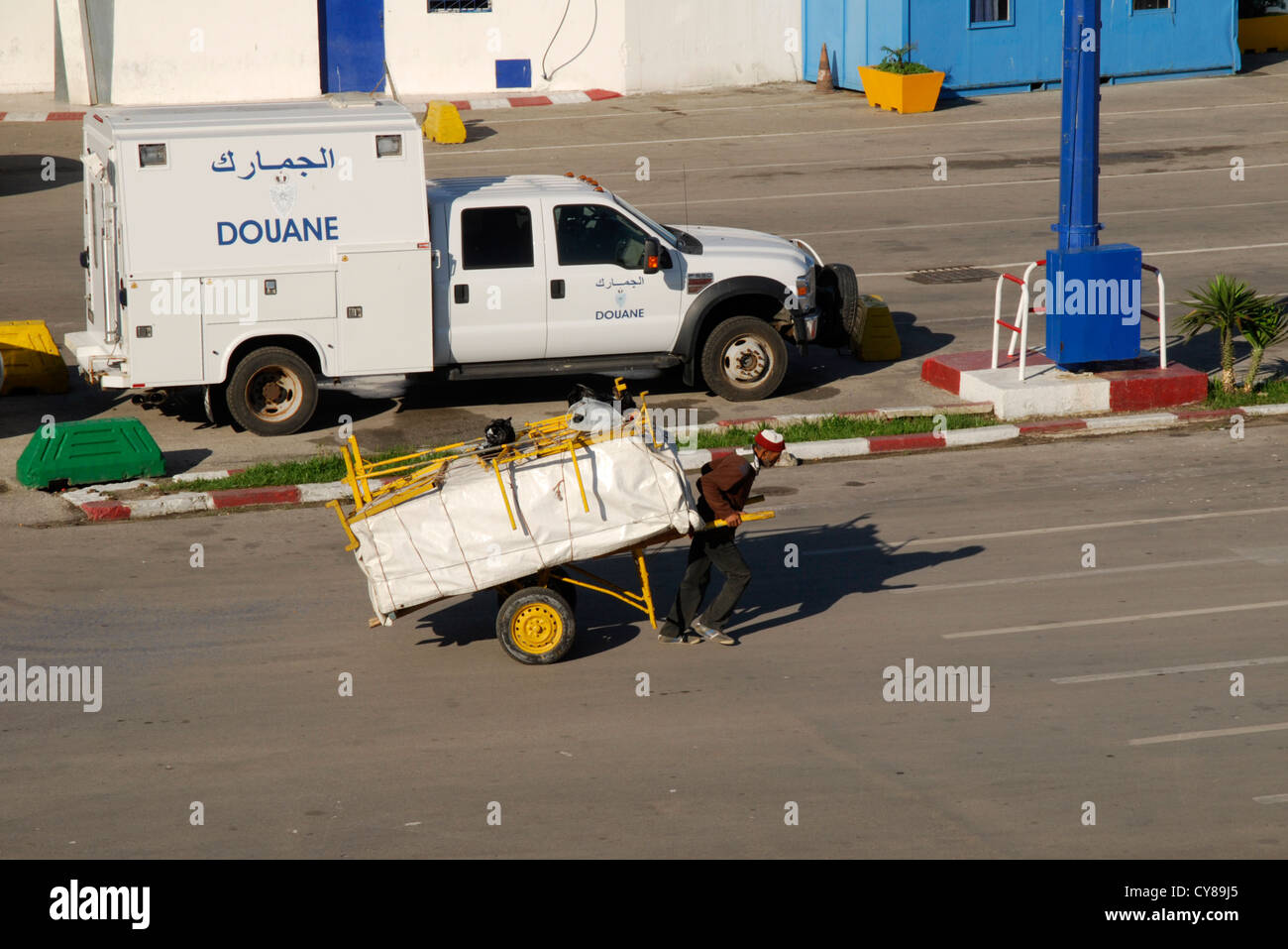 Porter Pulling Hand Trolley with Customs Van in Background. Portside view, Tangier, Morocco - Stock Image