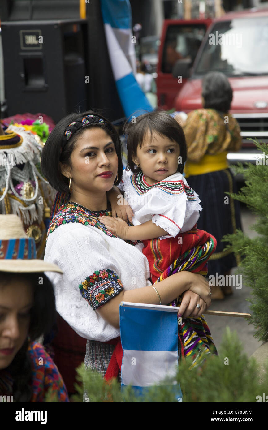 Hispanic Day Parade, New York City. Woman in traditional Guatemalan folk dress with child. - Stock Image