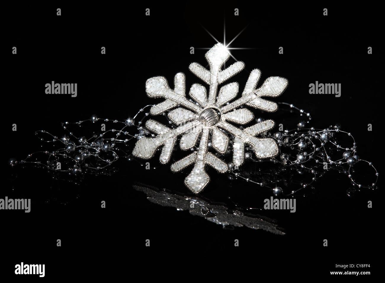 Glitter snowflake on black background. - Stock Image