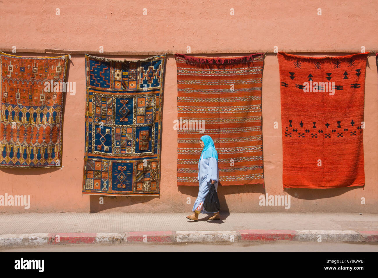 Woman walking by tapestry on the street, Marrakech, Morocco - Stock Image