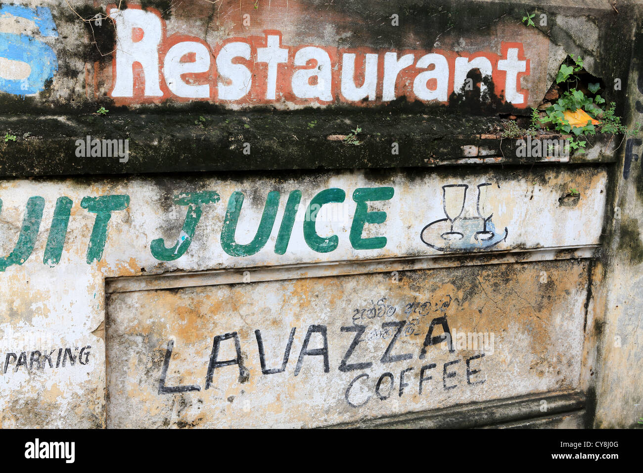 Fading restaurant sign painted on wall inside Galle Fort, Sri Lanka. - Stock Image