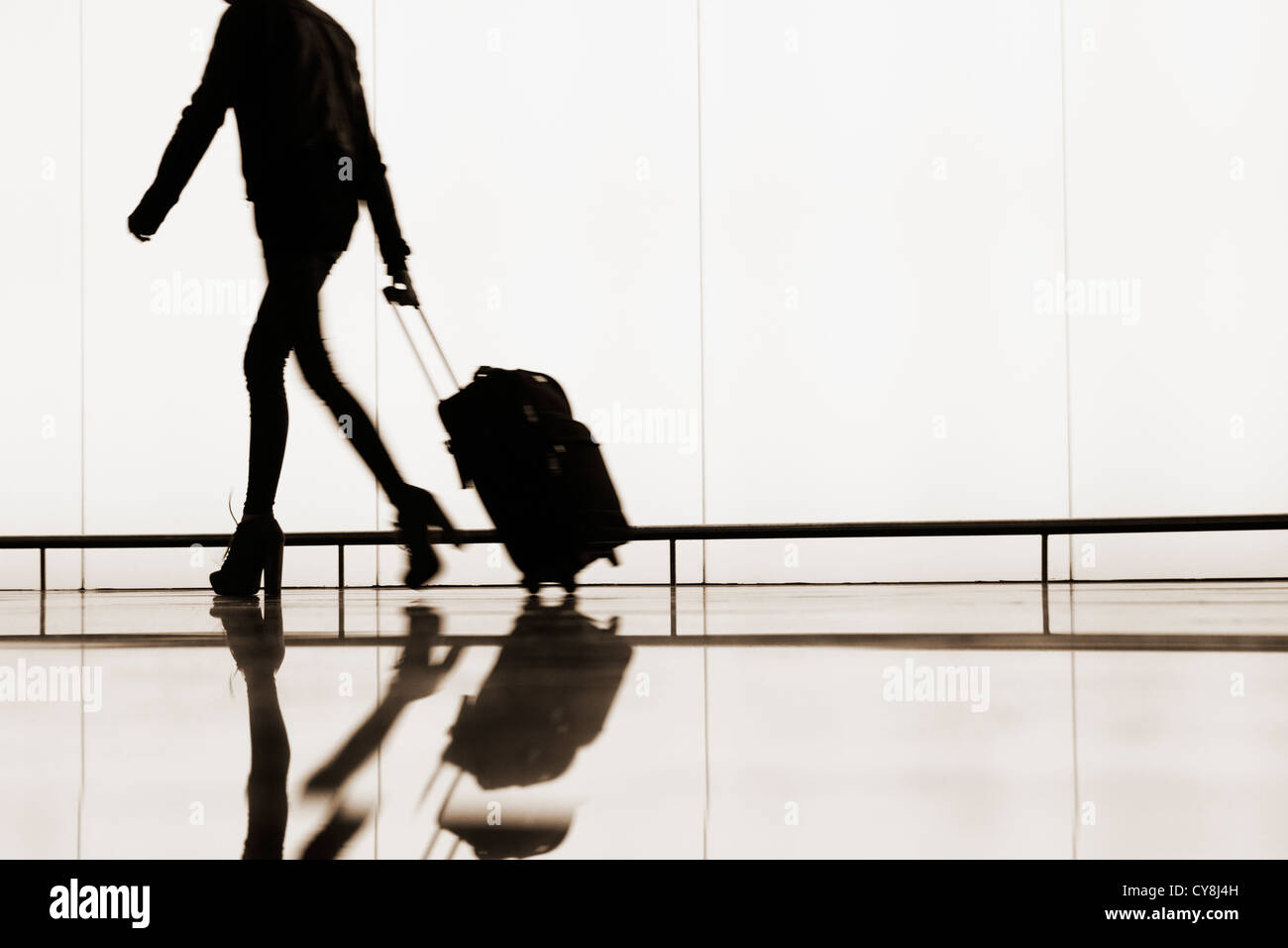 Woman with wheeled hand luggage at El Prat airport. Barcelona, Spain - Stock Image