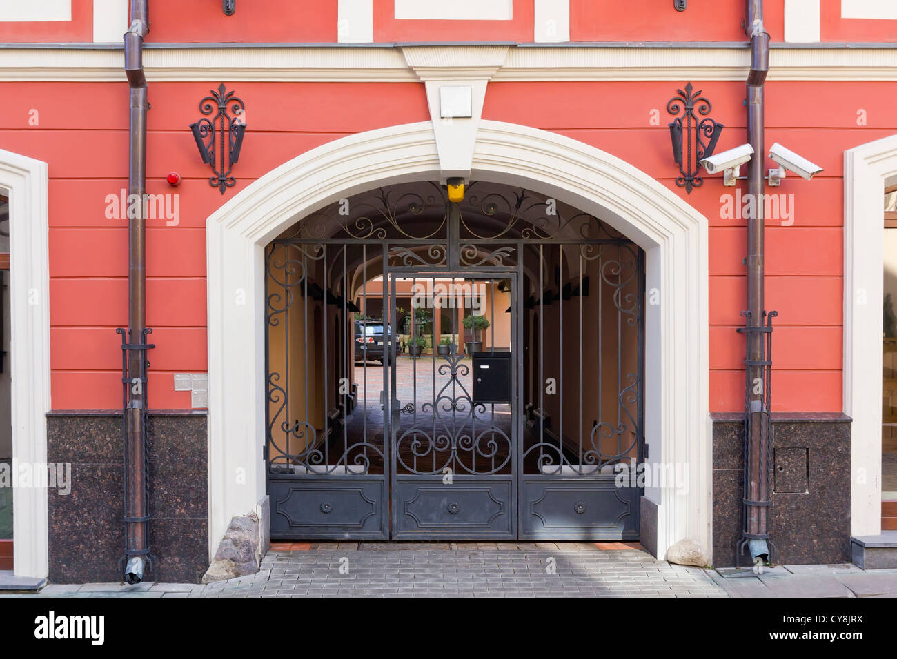 Video cameras monitor the entrance. Iron mass production gates bar the way. Outside the gates is a public domain - Stock Image