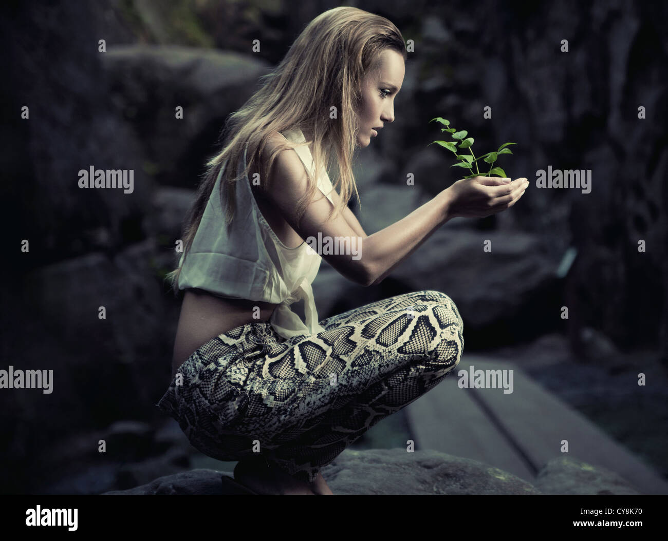 Beautiful young woman holding a plant - Stock Image