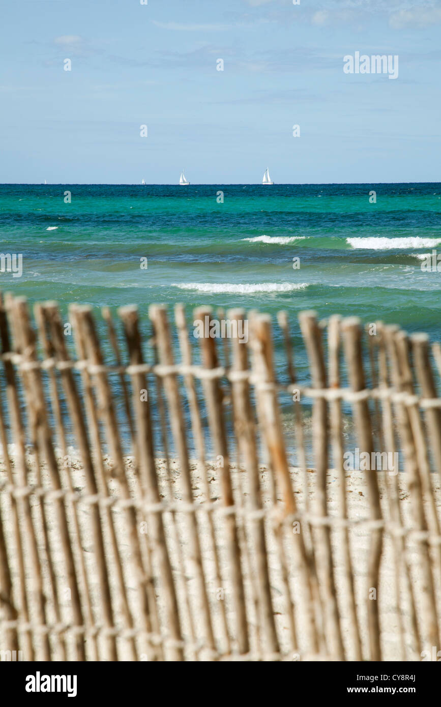 Tranquil beach scene with bamboo fence in foreground - Stock Image
