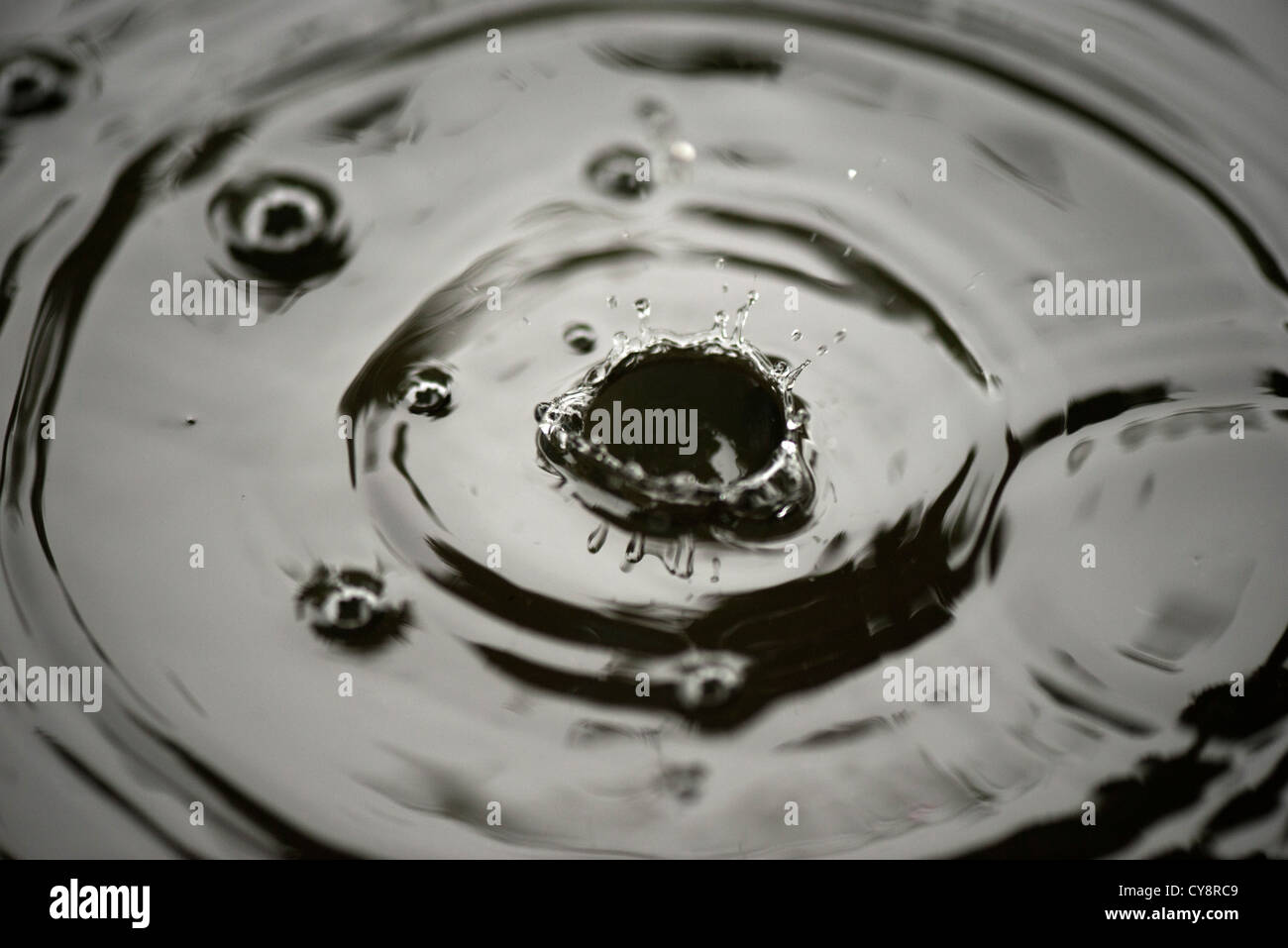 Drops splashing on water - Stock Image