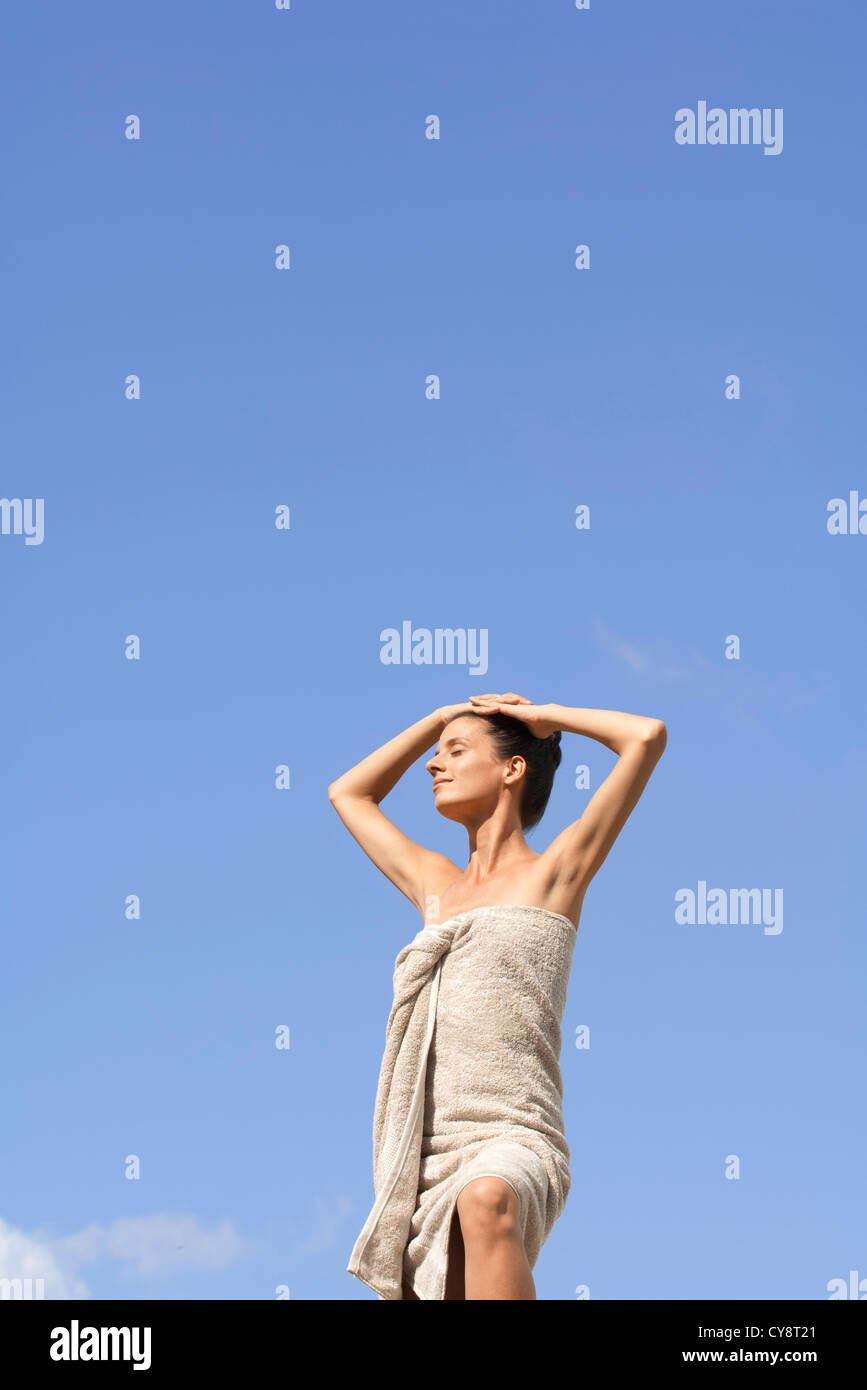 Mdi-adult woman standing wrapped in towel against blue sky, hands on head - Stock Image