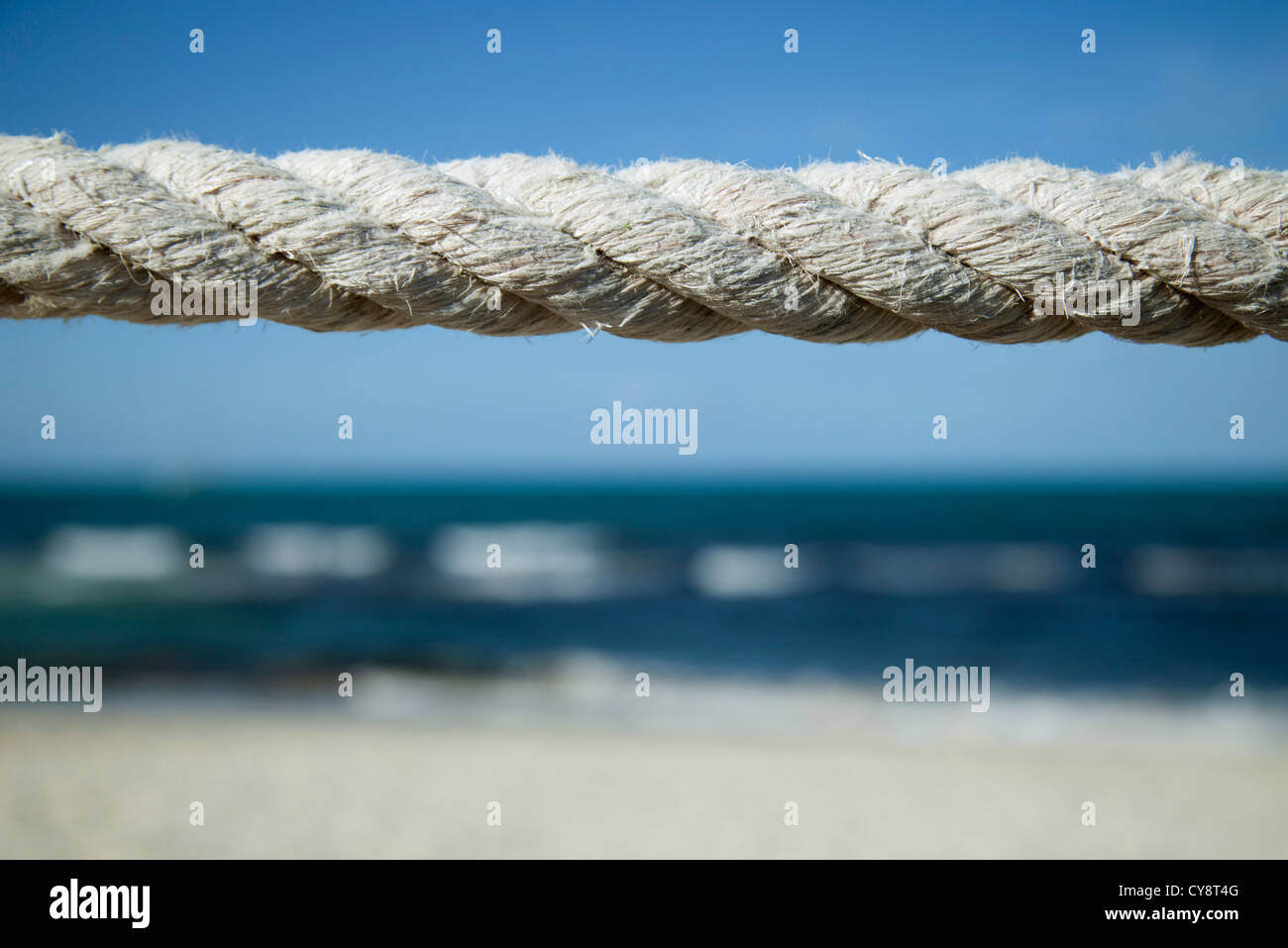 Close-up of weathered rope with beach in background - Stock Image