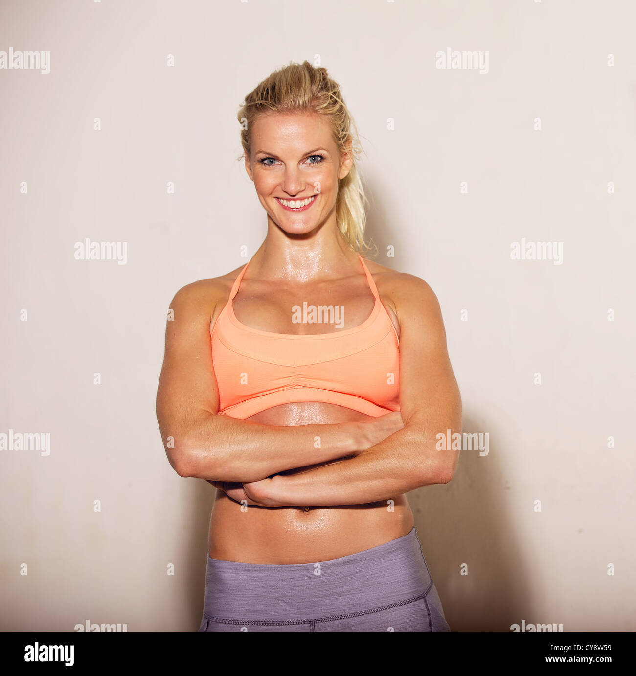 Smiling woman with arms crossed at the gym - Stock Image