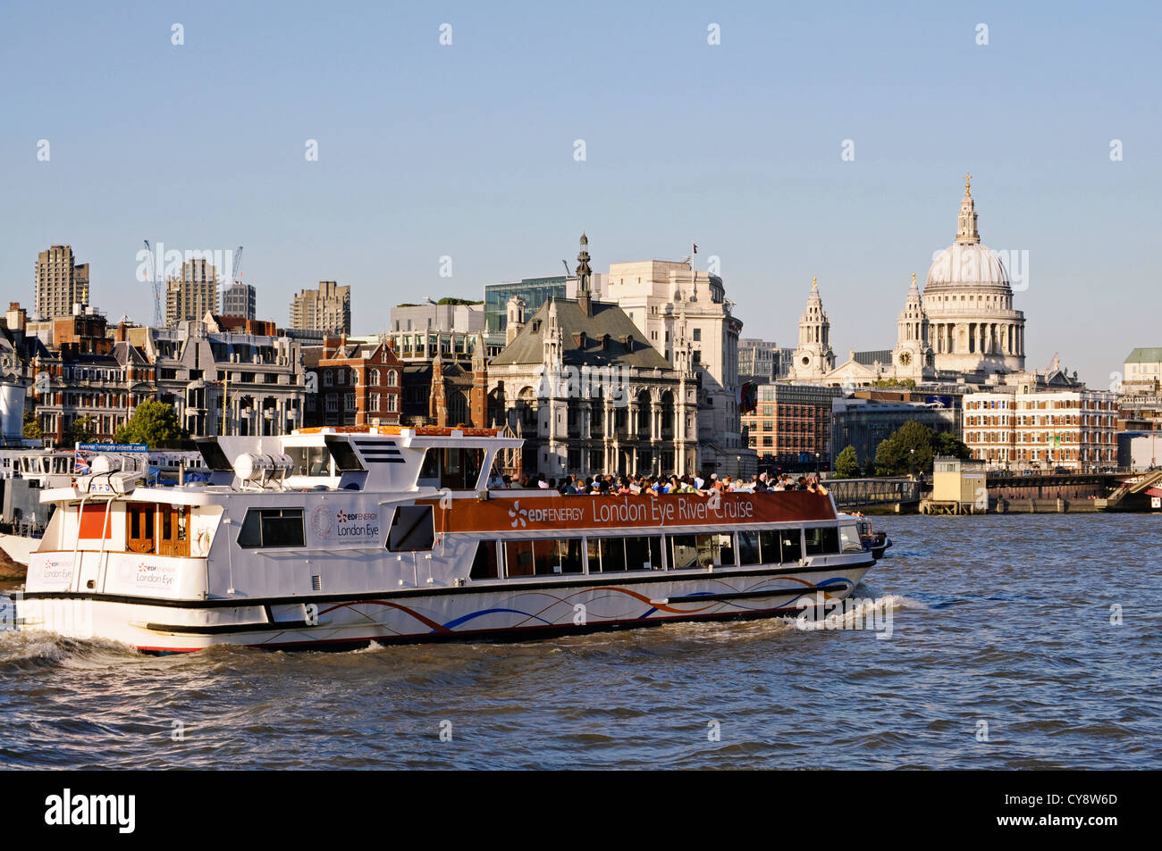 London River Thames cruise boat with St Pauls in the background at dusk. - Stock Image