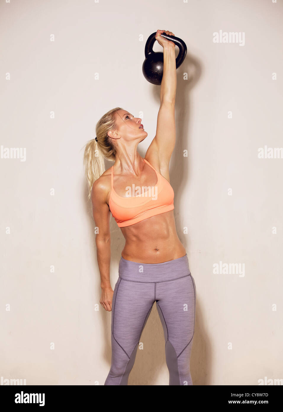 Strong woman lifting a kettlebell with only one hand - Stock Image