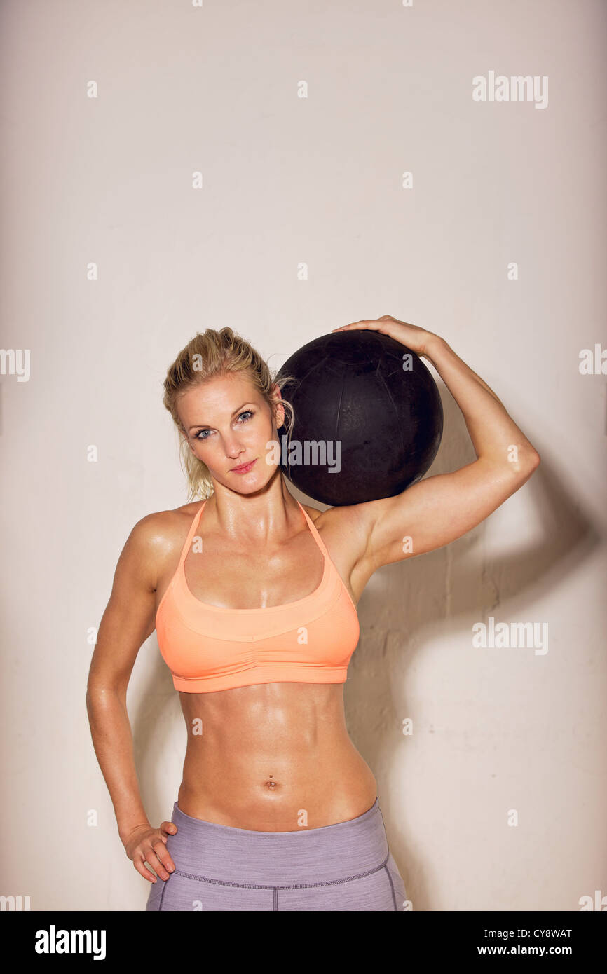 Portrait of a confident sport woman with a gym ball - Stock Image