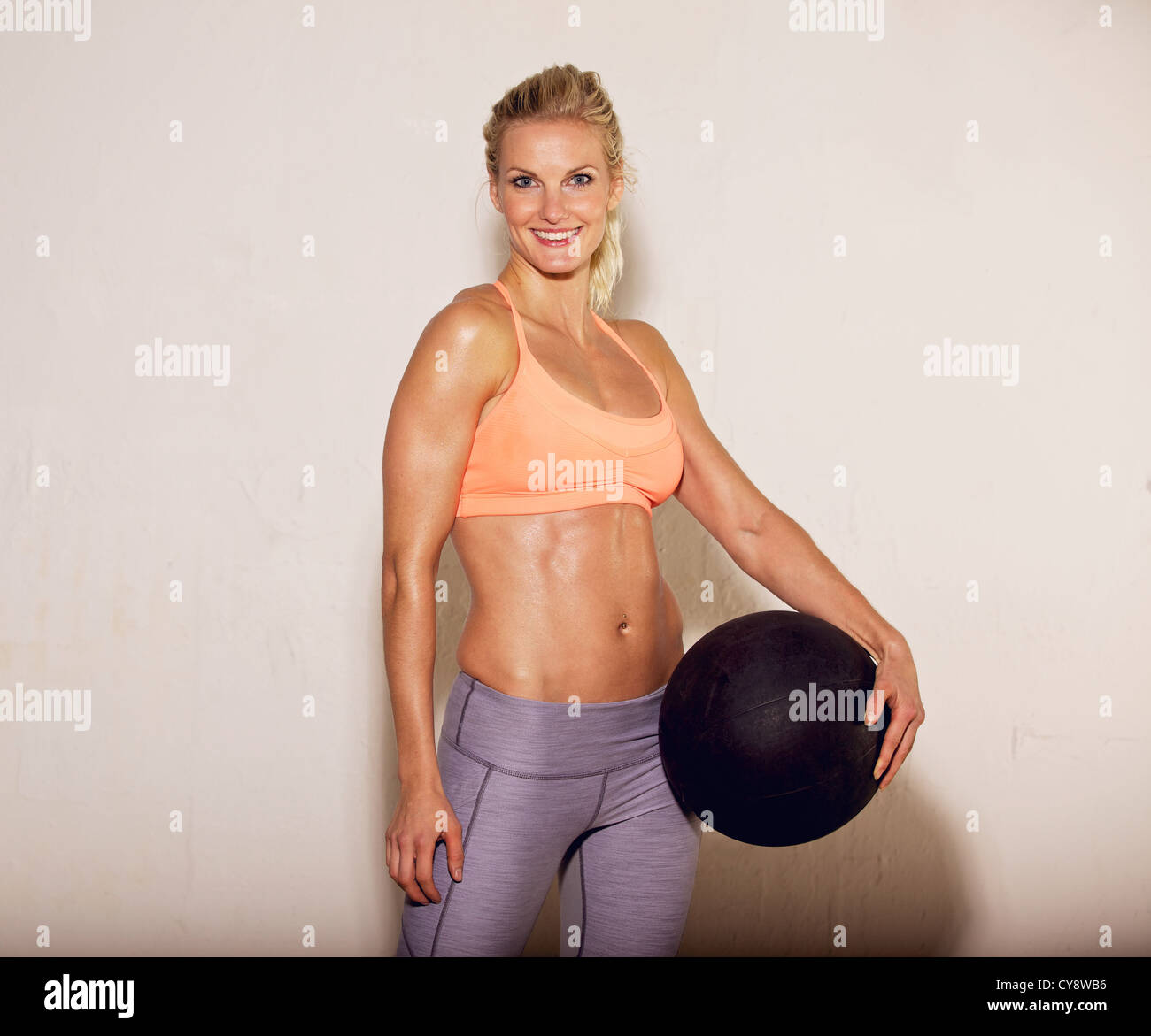 Beautiful pilates instructor holding a fitness ball - Stock Image