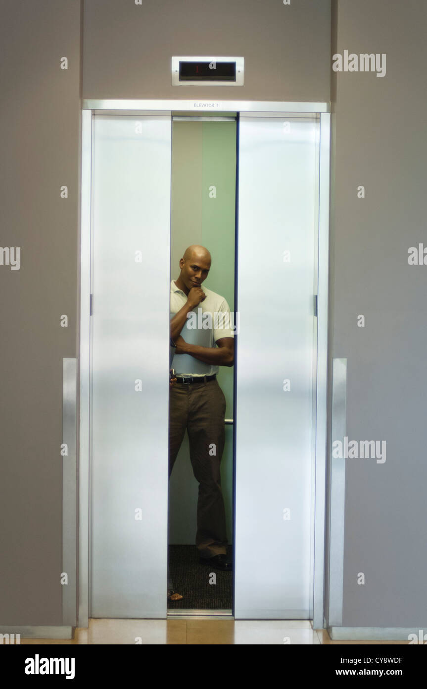 Young man standing in elevator with hand under chin doors closing & Young man standing in elevator with hand under chin doors closing ...
