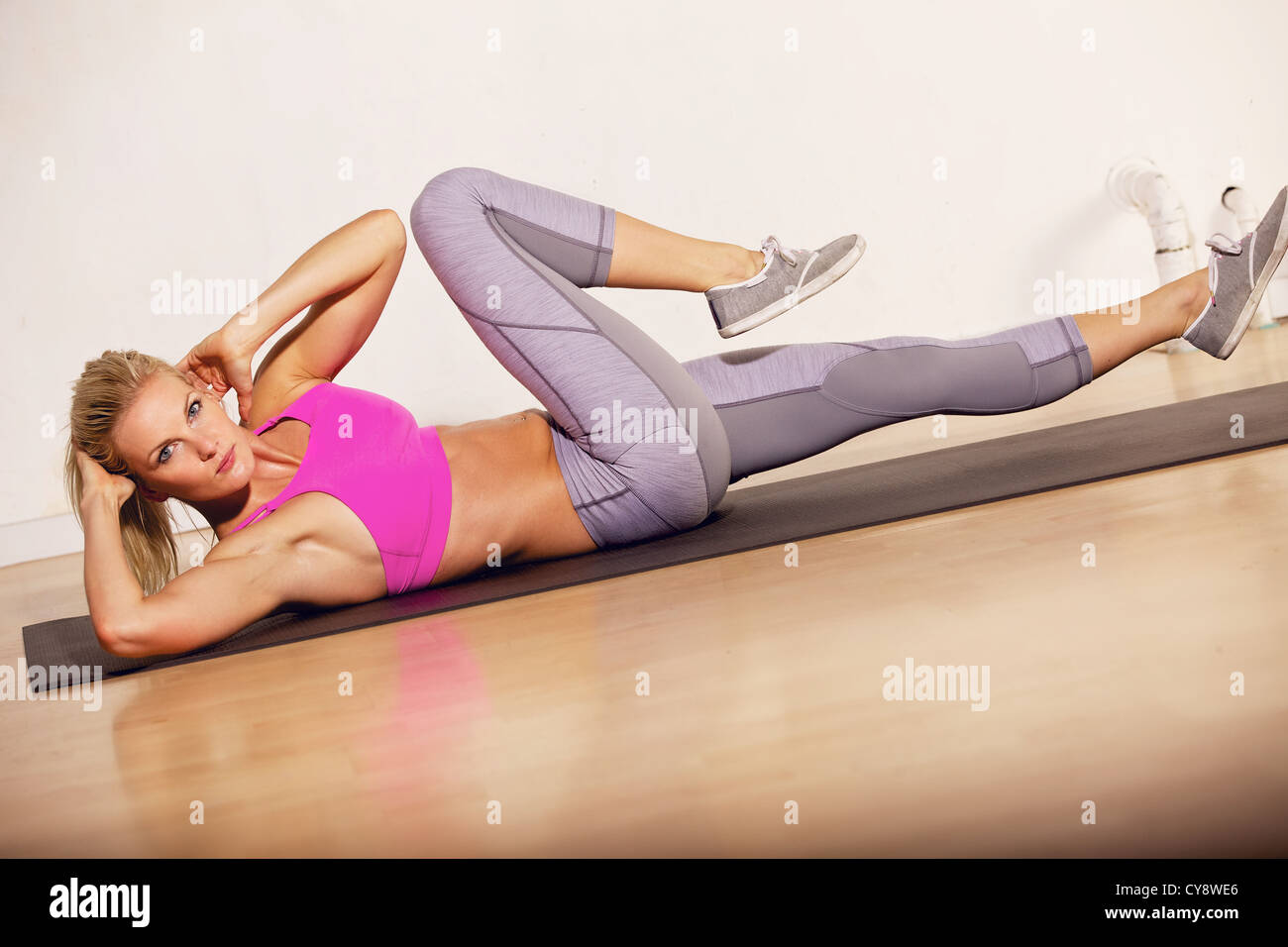 Gorgeous woman in the gym doing her situp exercise - Stock Image