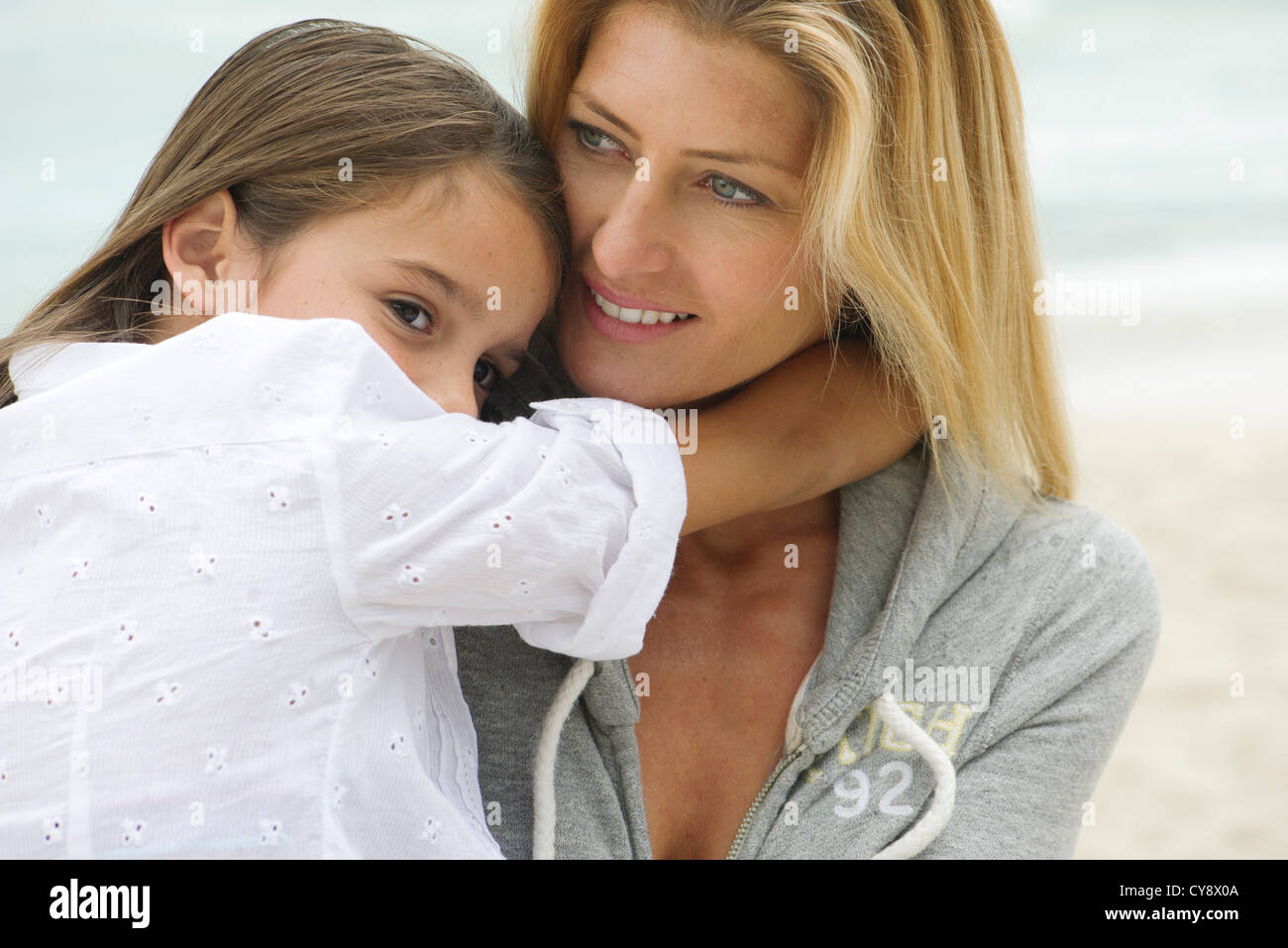 Mother and young daughter embracing outdoors - Stock Image