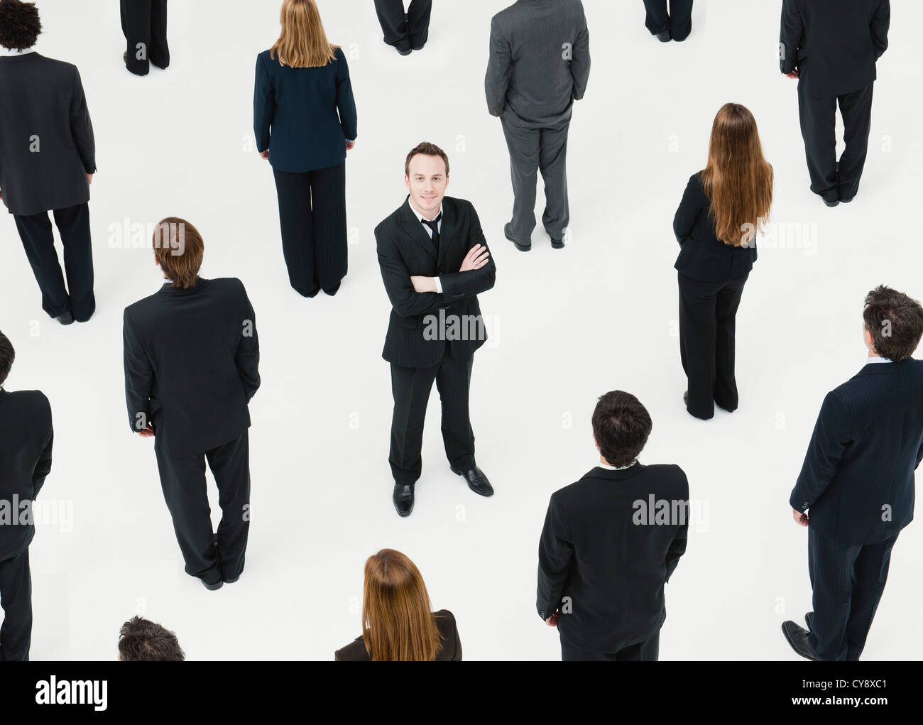 Businessman with arms crossed standing in midst of anonymously dressed business professionals - Stock Image