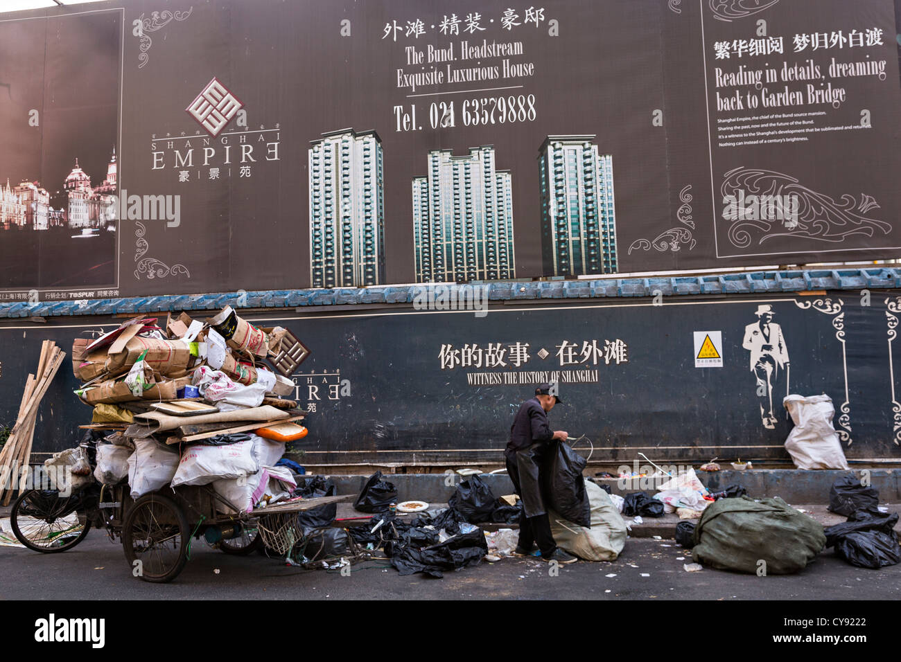 A street cleaner recycles paper in front of a luxury development in Shanghai, China - Stock Image