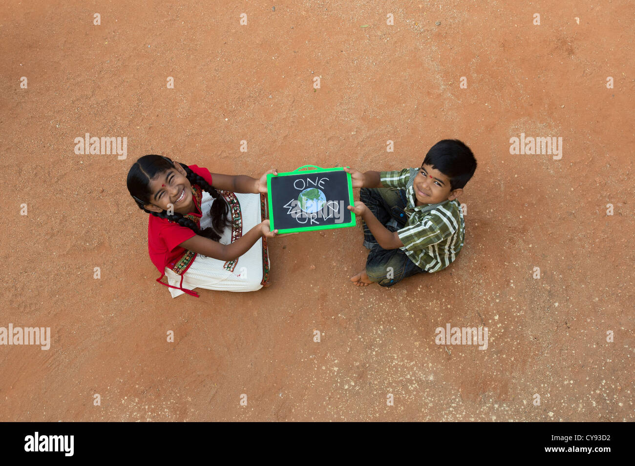 Indian village girl and boy with ONE WORLD written on a chalkboard in a rural indian village. Andhra Pradesh, India - Stock Image