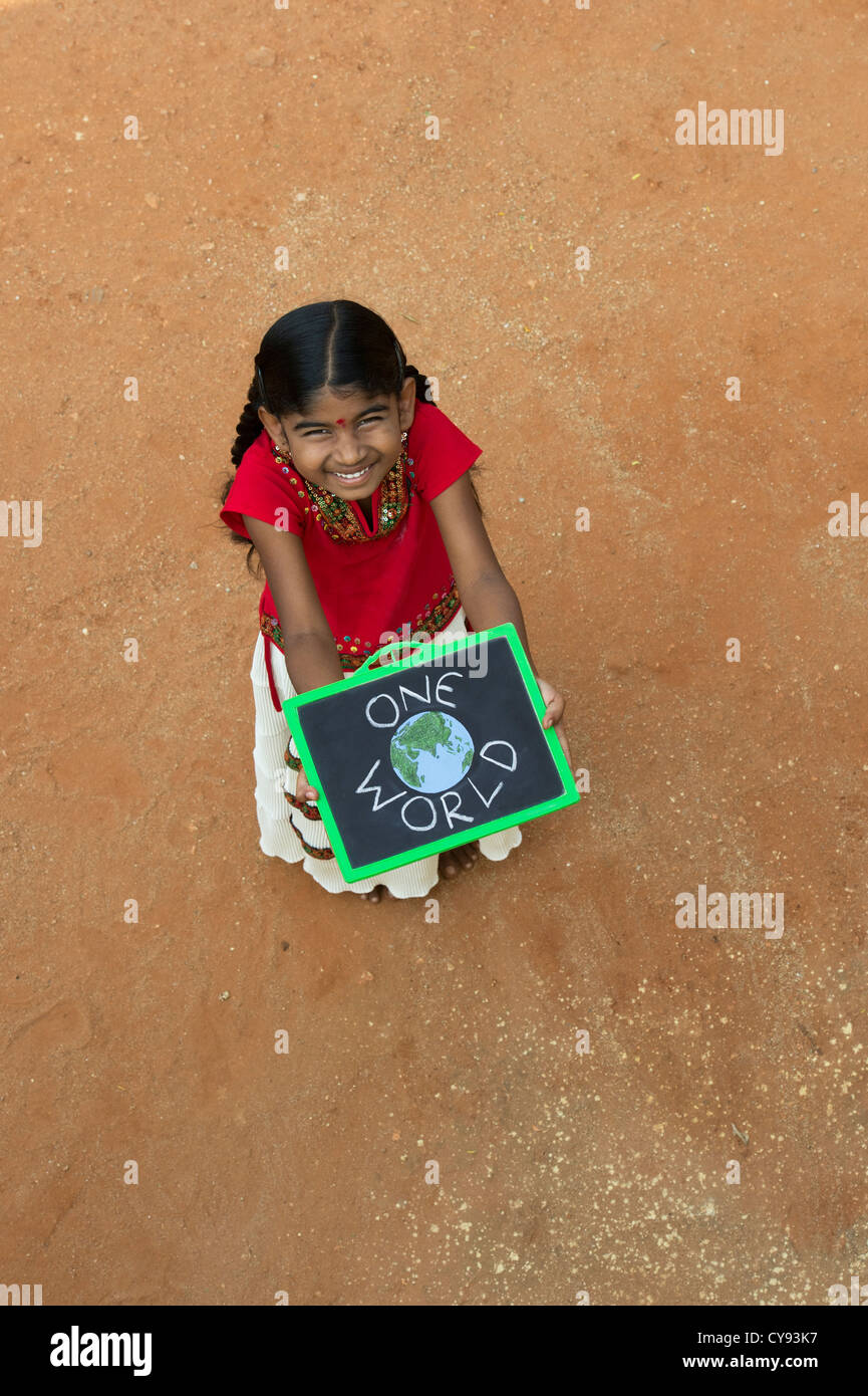 Indian village girl with ONE WORLD written on a chalkboard in a rural indian village. Andhra Pradesh, India - Stock Image