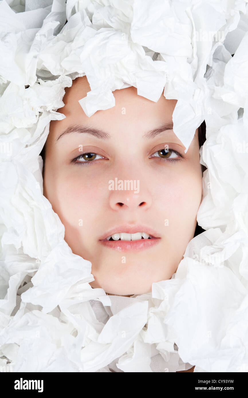 Ill Woman Face with Scrunched Paper Tissues - Stock Image