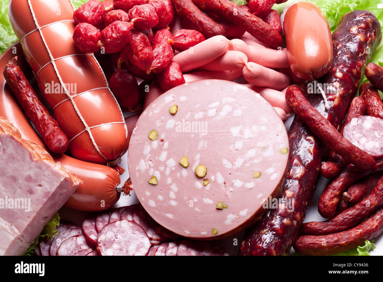 Meat and sausages on lettuce leaves. - Stock Image